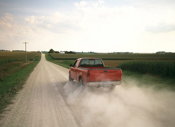 a red pickup truck driving down a country road